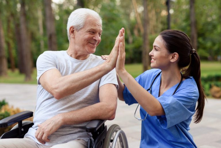A nurse and an old man in a wheelchair high five.
